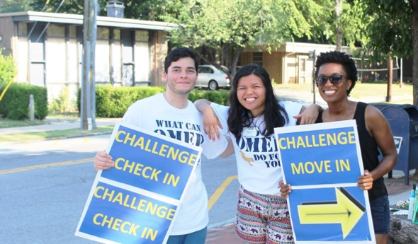 three students holding Challenge move in signs