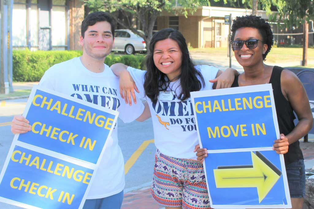 3 students with move in signs on challenge opening day