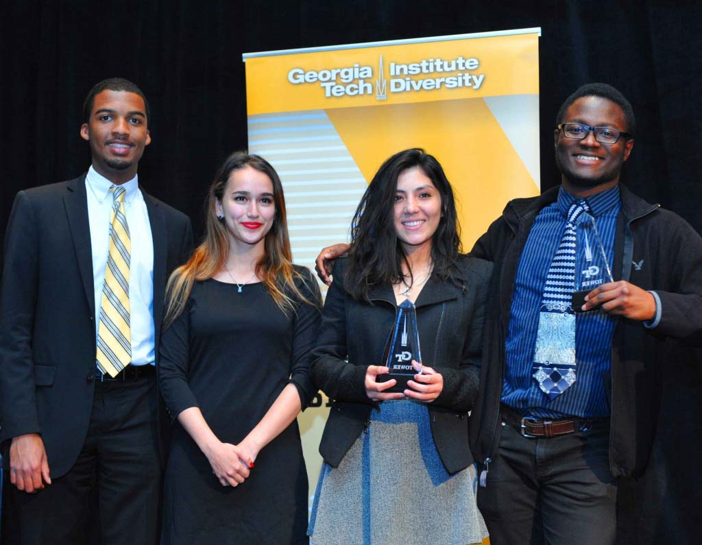 Four diverse students hold tower awards