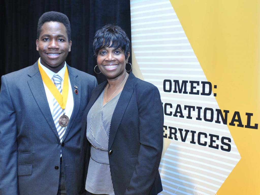 A son and his mom in front of an omed sign at the tower awards